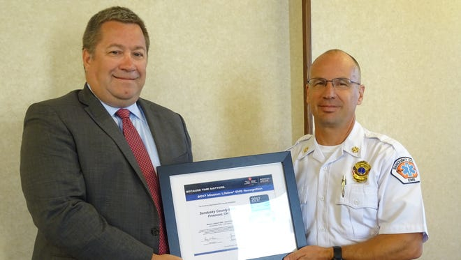 Alexander Kuhn, senior director of quality and system improvement for the American Heart Association awards gold plus achieve in cardiac services to Sandusky County EMS Director Jeff Jackson.