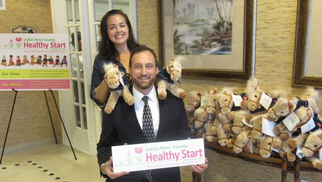 Andrea Berry, CEO of the Healthy Start Coalition,  accepts the donation of  Plush Ponies from Star dancer Richard Giessert of Wells Fargo Bank.