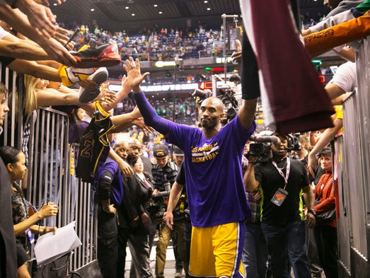 The Lakers' Kobe Bryant high-fives fans as he walks
