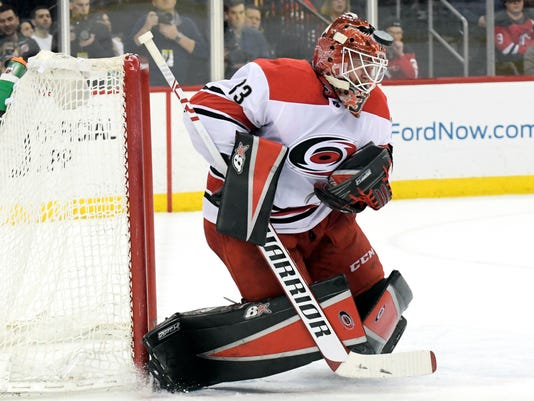 Carolina Hurricanes goaltender Scott Darling defects the puck during the second period of an NHL hockey game against the New Jersey Devils Thursday, Feb. 15, 2018, in Newark, N.J. (AP Photo/Bill Kostroun)