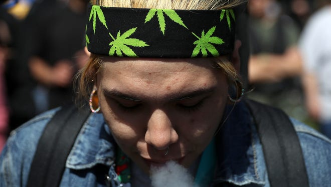 A marijuana user blows smoke during a 420 Day celebration in San Francisco. Recreational marijuana is legal in California - but for now, will remain illegal in Arizona.