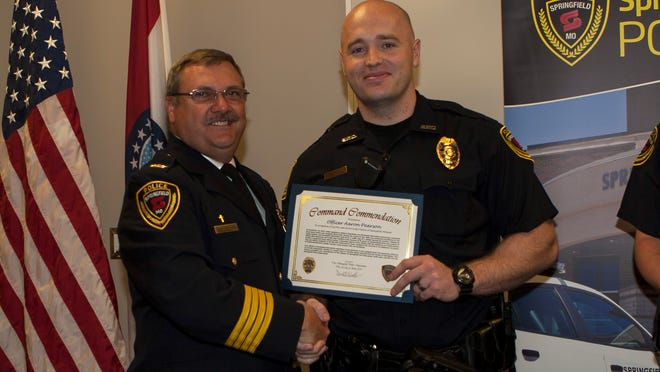 Police Chief Paul Williams gives Officer Aaron Pearson a command commendation last year for work the officer completed in late 2013 involved a suspected drug house within his assigned patrol beat.