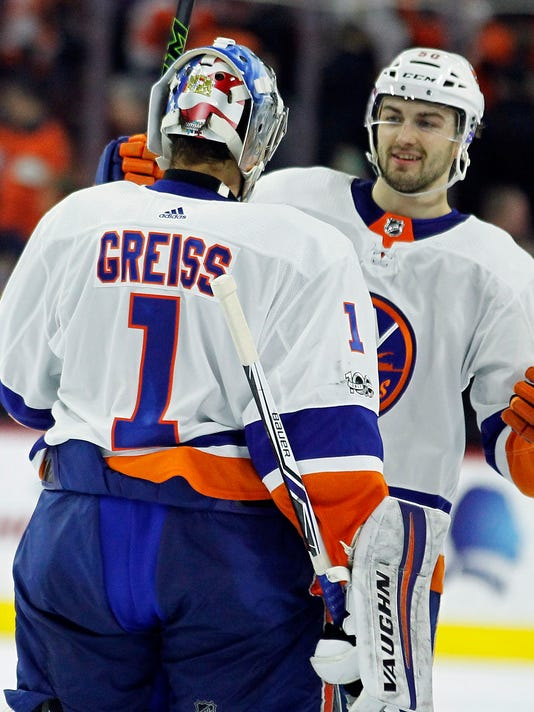 New York Islanders' Thomas Greiss is joined by Adam Pelech as they celebrate after winning during the overtime period of an NHL hockey game against the Philadelphia Flyers, Friday, Nov. 24, 2017, in Philadelphia. (AP Photo/Tom Mihalek)