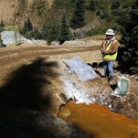 FILE - In this Aug. 14, 2015 file photo, an Environmental Protection Agency contractor keeps a bag of lime on hand to correct the PH of mine wastewater flowing into a series of sediment retention ponds, part of danger mitigation in the aftermath of the blowout at the site of the Gold King Mine, outside Silverton, Colo. Southwestern Colorado officials say they're ready to talk to the Environmental Protection Agency about a Superfund cleanup of inactive mines, including the one in Silverton that spewed millions of gallons of wastewater into rivers in August. (AP Photo/Brennan Linsley, file)