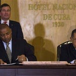United States Transportation Secretary Anthony Foxx and Cuba's Minister of Transportation Adel Yzquierdo Rodriguez, right, sign the airline transportation agreement as Assistant Secretary of State for Economic and Business Affairs Charles Rivkin, top left, looks on Tuesday in Havana. Cuba and the United States signed the agreement that will allow U.S. commercial airlines to begin operating flights to the island and vice-versa for the first time in decades.