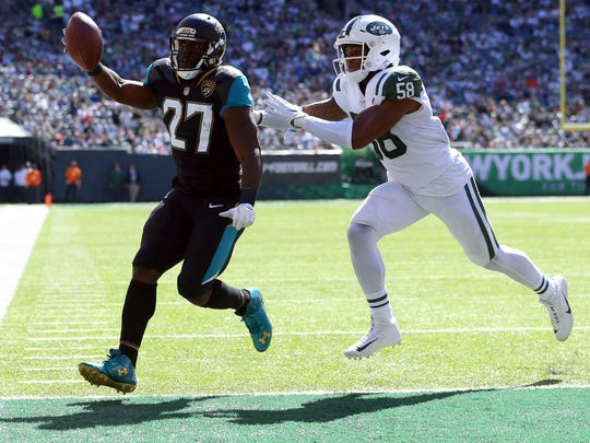 Jacksonville Jaguars running back Leonard Fournette runs for a touchdown against New York Jets linebacker Darron Lee during the first quarter at MetLife Stadium.