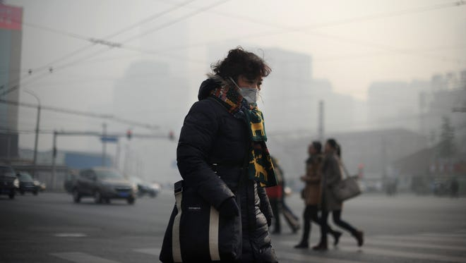 A woman wearing a face mask makes her way along a street in Beijing on Jan. 16, 2014.