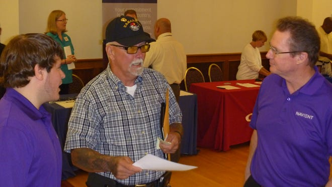 Navient human resources professionals Derek DiMaio (left) and Dave Anderson (right) talk to U.S. Marine Corps veteran Rex Perry about job opportunities with the company during an Aug. 25 job fair in Middletown.