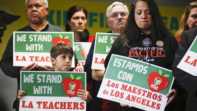 In this Jan. 13, 2019, file photo, student Leo Rittner Solomon, 6, front left, and parent Hilda Rodriguez Guzman, right, react as United Teachers Los Angeles president and teacher Alex Caputo-Pearl announces the nation's second-largest school district, Los Angeles Unified School District, was going on strike in Los Angeles.