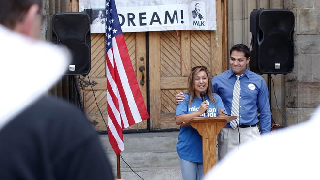 Cindy Garcia of Lincoln Park, left, is joined by Adonis Flores of Detroit during the Revive the Dream rally and march at St. Anne's Church.