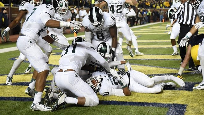 Michigan State defensive back Jalen Watts-Jackson (20) is surrounded by jubilant teammates after he recovered a fumbled snap on a punt in the closing seconds against Michigan and returned it for a touchdown. MSU won, 27-23.