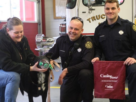 Thomas McDonald (center) and Chad Makowski (right) of the North Plainfield Fire Department try one of their new pet oxygen masks on Mouse, with the help of his owner, Kira Wright.