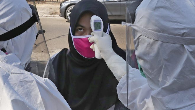 Health workers take the body temperature reading of a woman during a mass test for the new coronavirus in a neighborhood in Tangerang, Indonesia, Friday, July 17, 2020.