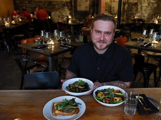 Chef and proprietor Nikita Sanches shows a bone marrow dish, front, pork chops with Brussels sprouts and garden salad. The restaurant is known for its international approach that skews a bit toward the Mideast.