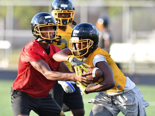 Junior quarterback Dequan Finn, left, threw for more than 1,900 yards last season for Detroit King, which has its sights set on winning its third consecutive Division 2 state championship.