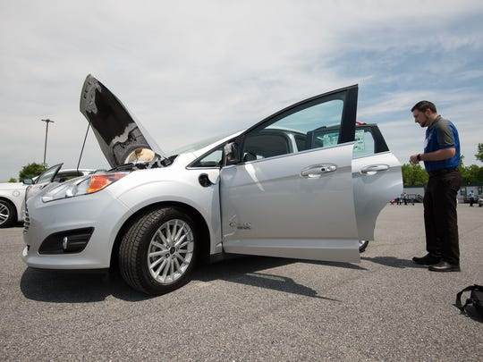 Sean Kelly, a sales consultant with Willis Ford in Smyrna, looks at a Ford C-MAX hybrid which was on display at the alternative fuels workshop at Dover Downs Casino in Dover.