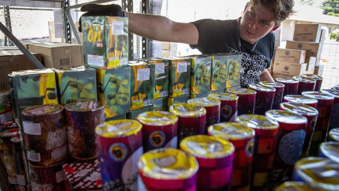 """Caleb Selander places a """"Dream On"""" firework in its place at the stand he is managing in the old SkateWorld parking lot in Springfield. [Andy Nelson/The Register-Guard] - registerguard.com"""