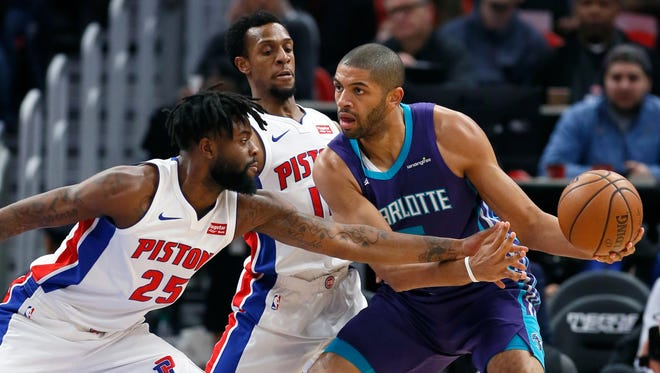 Pistons wing Reggie Bullock fouls Hornets wing Nicolas Batum as Pistons guard Ish Smith, center, helps defend during the first half Monday in Detroit.
