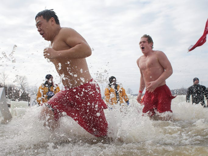 Participants take part in Polar Plunge, an event at Eagle Creek Reservoir that attracted 647 participants who entered a hole cut through foot-and-a-half thick ice, and raised $140,000 for Special Olympics Indiana, Saturday, March 1, 2014.