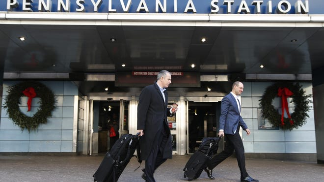In this Jan. 6, 2016 file photo, two men roll their suitcases from the exit of Pennsylvania Station in New York. Gov. Andrew Cuomo hopes a new agency will help smooth the way for massive state construction projects like the planned $29 billion mass transit overhaul in New York City, but critics worry about a power grab by the Democratic leader.