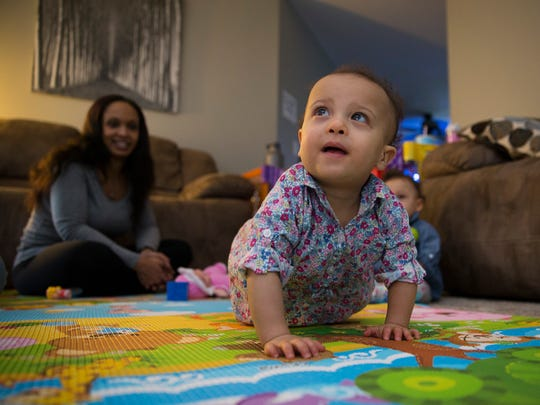 One year old Aria Kudelin explores while twin Natalie plays with a rattle.  Both twins beat the odds to survive after being born at 23 weeks and less than a pound each. A fundraiser for the family is upcoming in a few weeks.