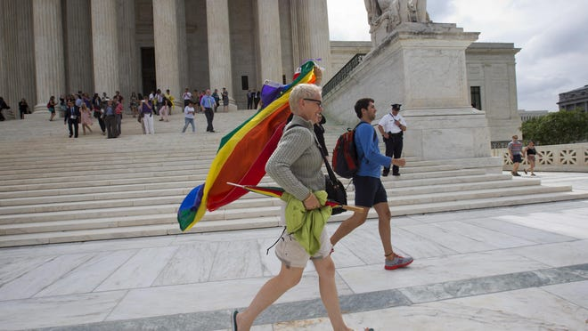 A woman who was inside the Supreme Court on Friday runs across the court plaza in as she celebrates after the court declared that same-sex couples have a right to marry anywhere in the US.