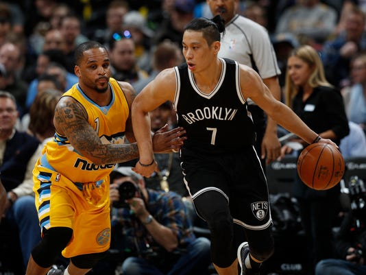 Brooklyn Nets guard Jeremy Lin, right, works the ball inside to the net as Denver Nuggets guard Jameer Nelson defends in the first half of an NBA basketball game Friday, Feb. 24, 2017, in Denver. (AP Photo/David Zalubowski)