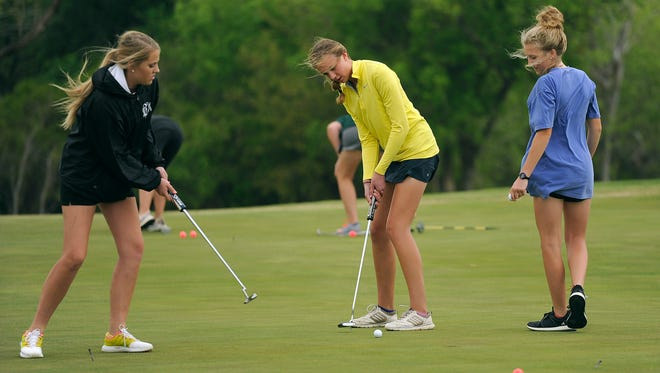 Wylie golfers Maddi Olson (center) and Arin Zachary (left) practice their putting as teammate Brylee Valentine looks on during the Bulldogs' practice on Tuesday, March 28, 2017, at Diamondback Golf Club.