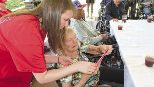 Veterans OutReach volunteer Amy LaGrone presents veteran Opal Brown with a birthday card and $25 during the Mississippi Veterans Home's April birthday party.