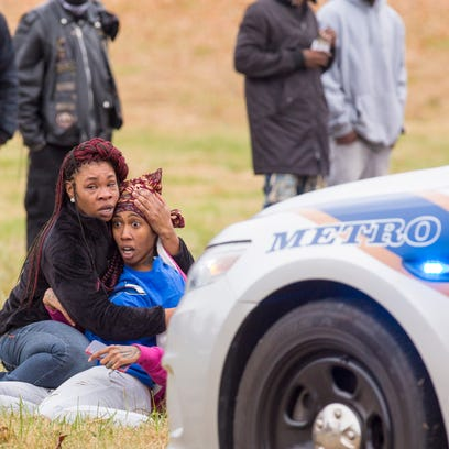 A woman is restrained after reacting to knowing a shooting