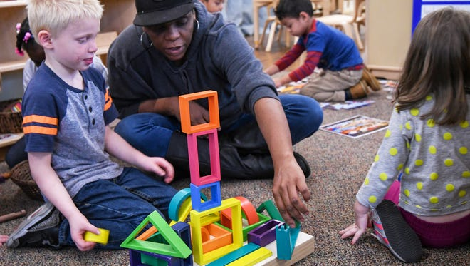 A preschool teacher helps a student build Monday, Oct. 23, 2017 at the Cincinnati Early Learning Center in Price Hill. Each classroom at CELC has at least two teachers to help ensure that children get the attention they need.