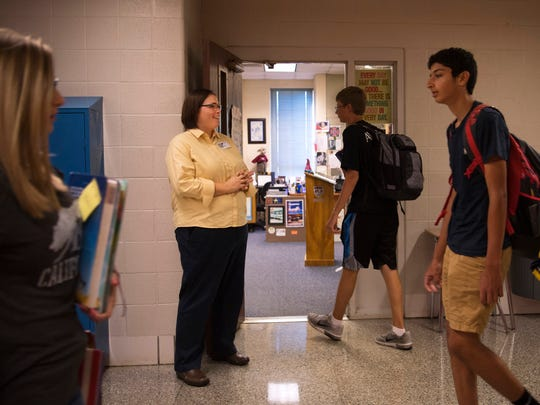 Castle High School U.S. History teacher Emily Garrett greets students in the hallway during a break in classes Thursday morning.