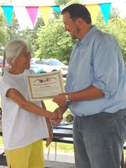 Evelyn Miller receiving a certificate of recognition