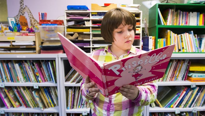 Annalysa Hubert, 9, reads a book in the library at Homeward Bound in Phoenix Dec. 1, 2015. The shelter is a grant recipient for Season for Sharing.
