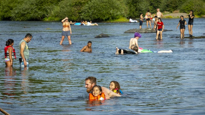 Aaliyah Nutter, Mathew Lyvesay and Alexis Nutter cool off in the popular D Street swimming hole in the Willamette River in Springfield in June. Temperatures may head into the triple digits this weekend. [Andy Nelson/The Register-Guard file] - registerguard.com