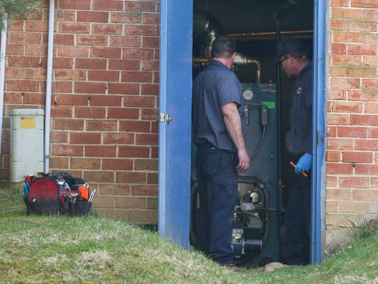 Technicians work Saturday in the utility room of an