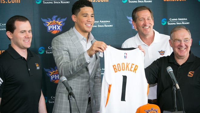 Phoenix Suns GM Ryan McDonough, left, first-round NBA draft pick Devin Booker, head coach Jeff Hornacek and President of Basketball Operations Lon Babby hold up Booker's new basketball jersey at US Airways Center in Phoenix on Friday, June 26, 2015.