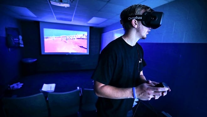 University of Memphis backup Quarterback Jason Stewart shows how the team uses virtual reality goggles to help learn plays during an interview at the Murphy Athletic Complex.