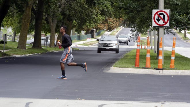 Motorists and a pedestrian drive and walk on a section of North Avenue that has been repaired with a new system the City of Sheboygan has begun using Tuesday Aug. 18, 2015, in Sheboygan.