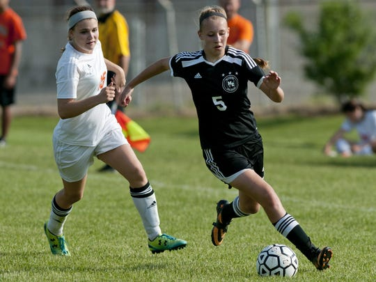 Marine City sophomore Emilie Andrews gets past Armada senior Amy Henderson during a Division 3 district soccer game Friday, May 29, 2015 in Armada.