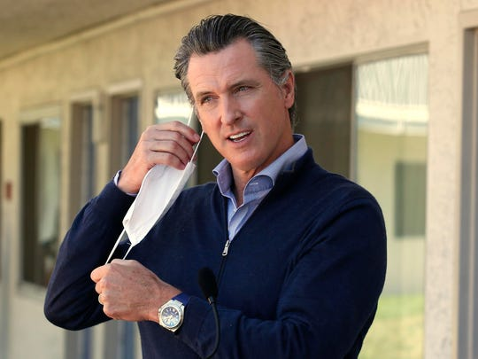 California Gov. Gavin Newsom removes his face mask before giving an update during a visit to Pittsburg, Calif.