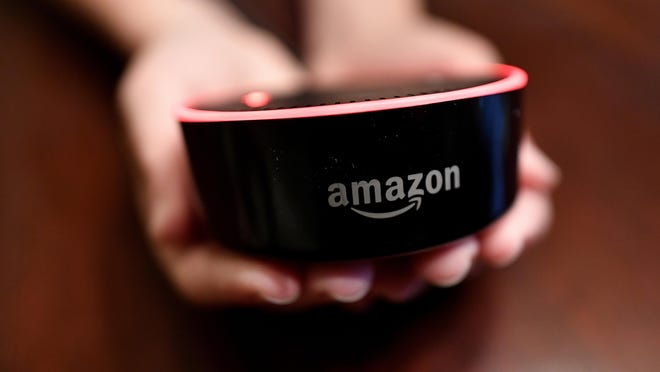 A child holds his Amazon Echo Dot in Kennesaw, Ga. Amazon updated its voice assistant with a feature that can make Alexa more kid-friendly. When the FreeTime feature is activated, Alexa answers certain questions differently.