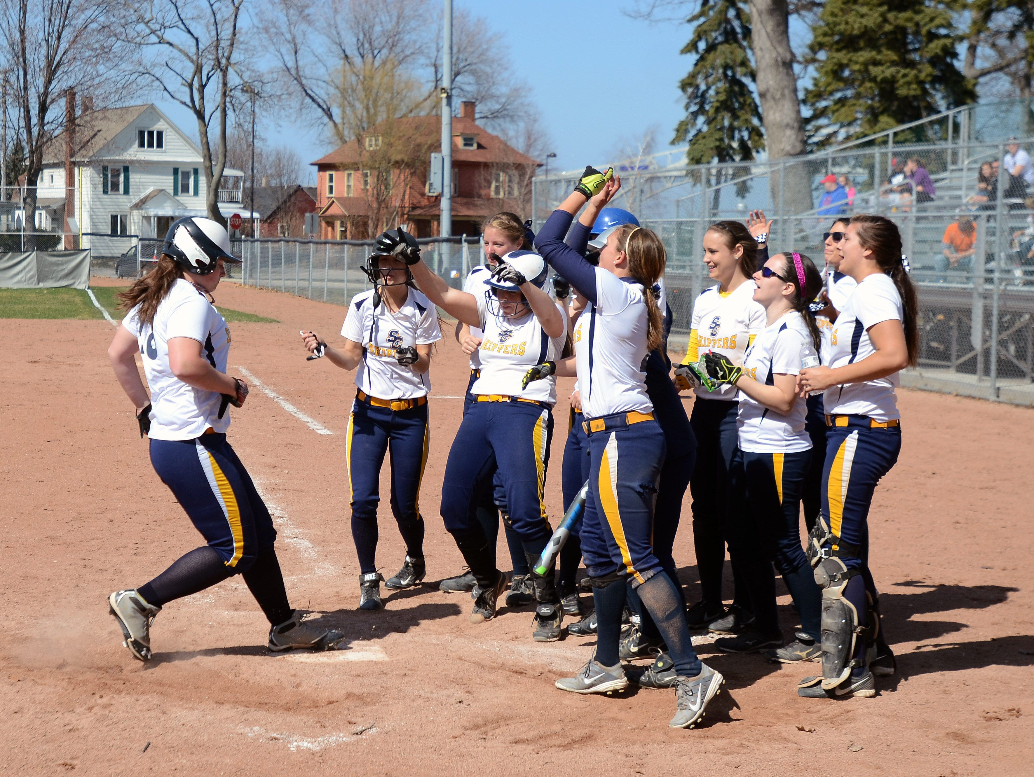 Alyson Edgemon's Skipper teammates meet her at home plate after her home run Sunday during a game against Oakland Community College at Pine Grove Park.