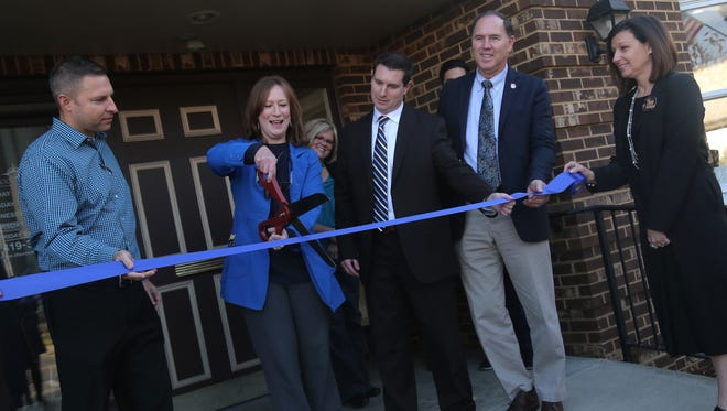Dr. Marisa Miller (second from left) cuts the ribbon at the open house for Discovery Dental in downtown Shelby on Thursday.