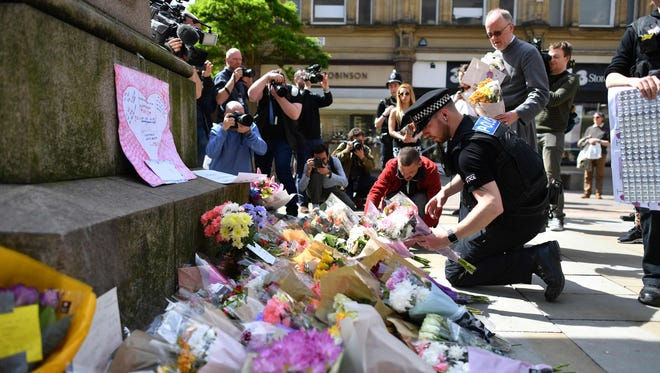 Police officers relocate tributes in St Ann's Square in Manchester, England May 23, 2017, that were laid as a mark of respect to those in killed and injured in a deadly terror attack at the concert the night before.