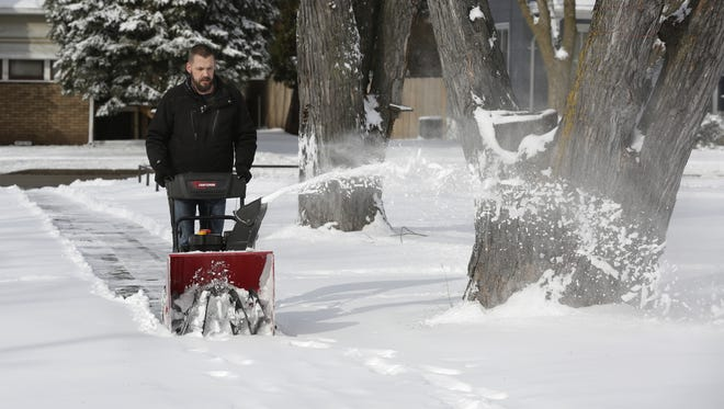 Regan Hill snow blows his sidewalk on Powers Street at New York Avenue as the Oshkosh area received about 3 inches of snow that began in the early morning hours and continued until early afternoon March 1, 2016.