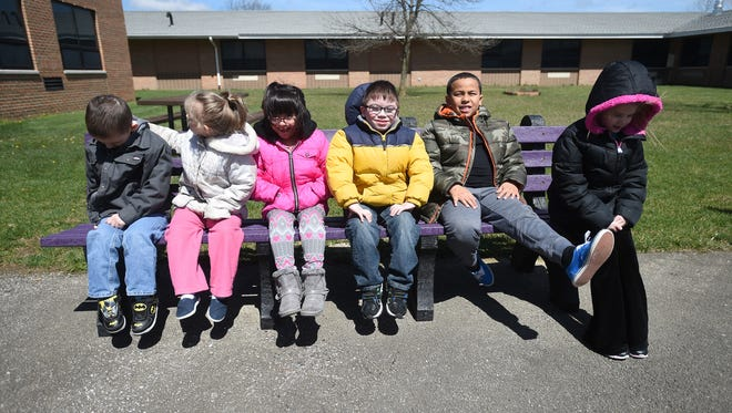 Elijah Mobley, left, Catherine Clark, Yuvia Cervantes-Leos, Phillip Whitehead, Caiden Payne and Irelynd Legg, right, sit together on a bench Friday, April 7, 2017 at Cresdale Elementary School. The bench and a table were made in memory of classmate Alexis Patterson. Students organized a collection of plastic bottle caps that were then used to make a bench and table in purple, Alexis Patterson's favorite color.