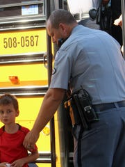 A South Carolina Highway Patrol trooper helps a student off of a school bus at Oakdale Baptist Church after a shooting Wednesday at Townville Elementary School.