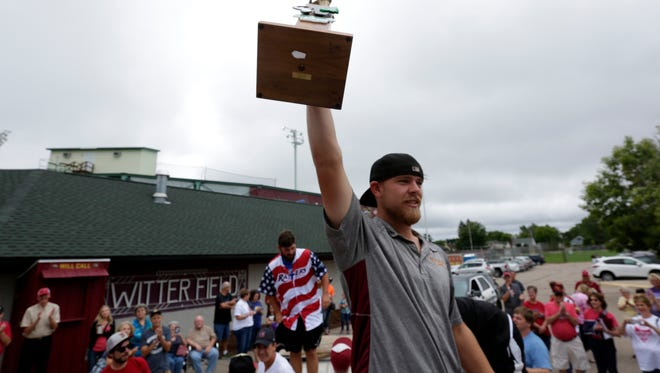 Wisconsin Rapids Rafters John Jaeger lifts up the Northwoods League trophy and shows it to fans during the celebration for the Northwoods League Championship win by the Rafters in August.