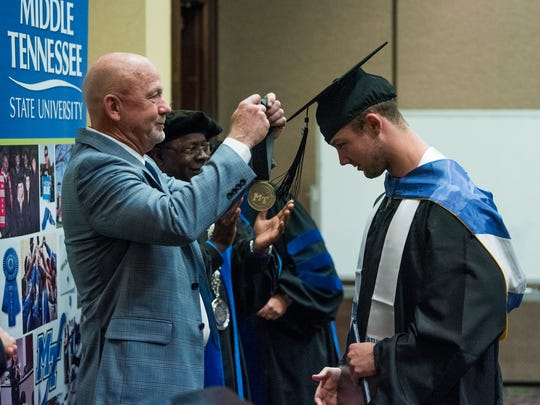 Middle Tennessee State University football coach Rick Stockstill places a medal on quarterback Brent Stockstill as the senior members of the MTSU football team are given a graduation ceremony at the team hotel in Montgomery, Ala. on Friday December 15, 2017.